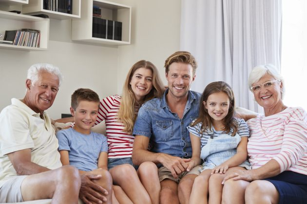 Portrait Of Multi Generation Family Sitting On Sofa At Home